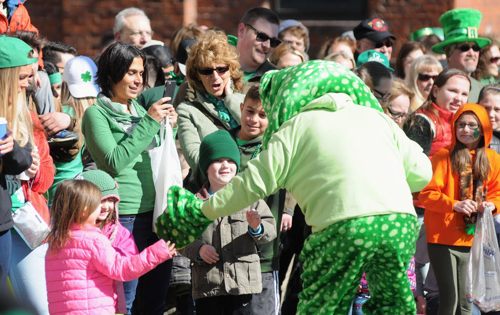 A Utica Zoo frog mascot visiting with and high fiving children along Genesee St.  (Sentinel photo by Makenzi Enos)