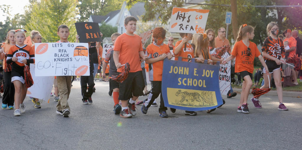 "STARTING YOUNG — Students from ""Fort Joy"" Elementary School with handmade signs and with faces painted orange and black walk in the parade prior to Friday's homecoming football game.  (Sentinel photo by Makenzi Enos)"