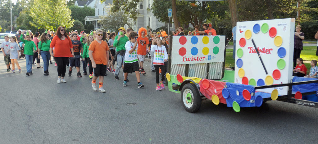 ALL THE RIGHT MOVES — Members of the Staley Upper Elementary community march with their Twister float in Friday's parade, hoping to inspire the RFA Black Knights to show off their own moves at the stadium later in the evening.  (Sentinel photo by Makenzi Enos)