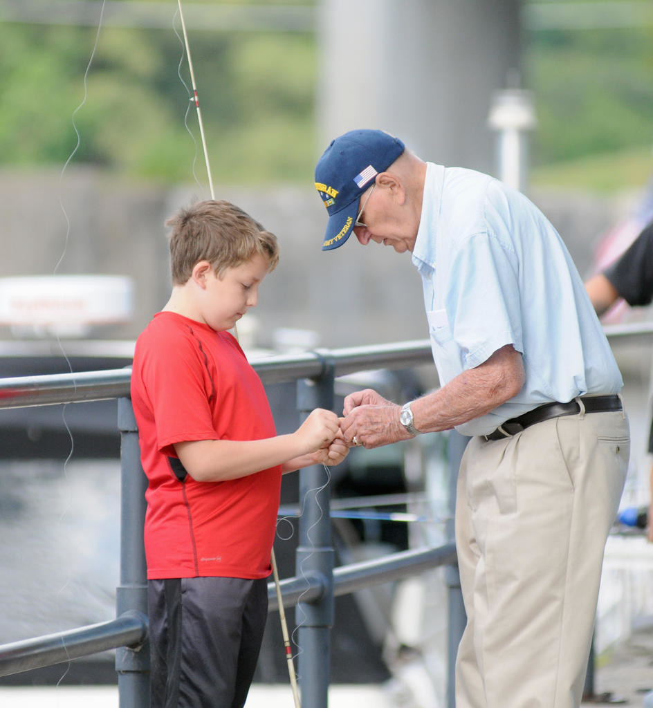 George Coote, Sr. helps his friend's grandson Jack Weinert, 12, set up his fishing line for the fishing derby. (Sentinel photo by Makenzi Enos)
