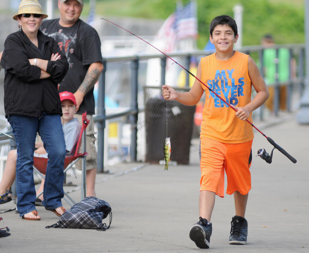 Evan Melendez 11 proudly walks with his catch of the day to the judging station during the fishing derby.  (Sentinel photo by Makenzi Enos)