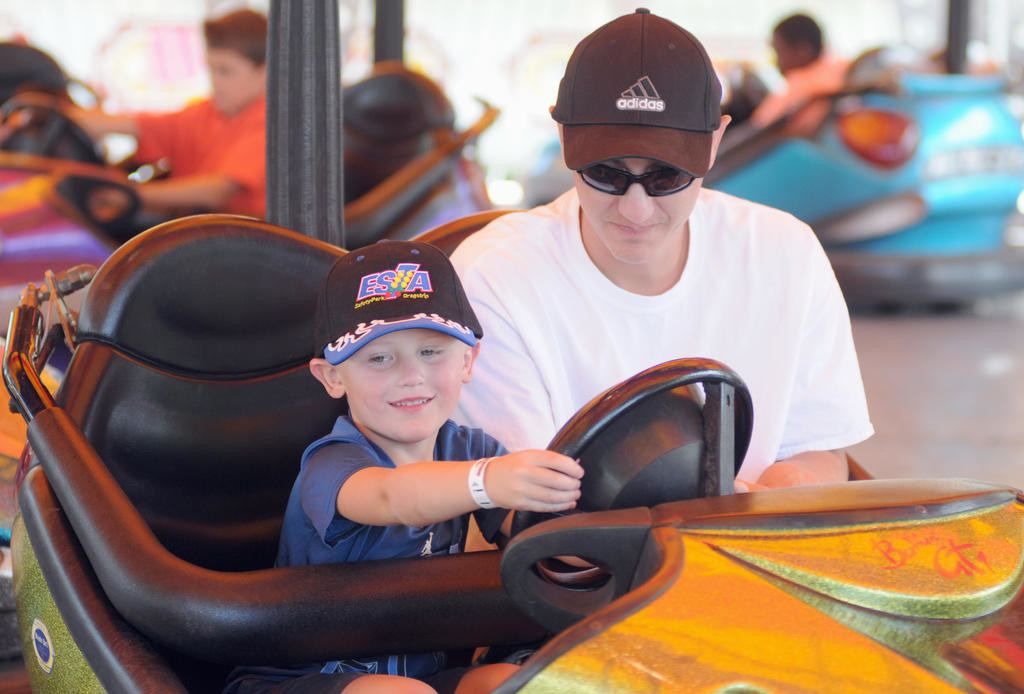 Ryan Beckwith rides the bumper cars with his son Ryan Beckwith, Jr. behind the wheel.  (Sentinel photo by Makenzi Enos)