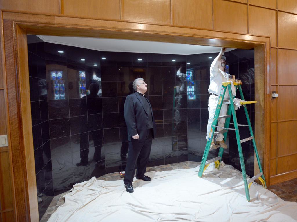 FIT FOR A MASTERPIECE — The Rev. Paul F. Angelicchio watches Mark Nellenbach, owner of M&M Painting and Wallpapering, put finishing touches on a display area at St. John the Baptist Church on East Dominick Street. The recessed area will host a replica of The Pietà, a sculpture by Michelangelo that sits in The Basilica of St. Peter in Vatican City, Rome, Italy. A former Roman is financing the sculpture, one of 11 he is funding and one of 112 that will be made. It will be unveiled April 26. Story, photo, page 2.  (Sentinel photo by John Clifford)