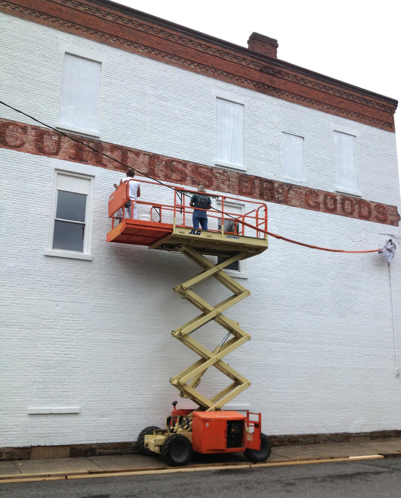 MEN AT WORK — Two workers on a scaffold paint the wall of the Camden VFW post white to give artist Jane Grace Taylor a clean canvass to work on to paint the Camden Continentals Fife and Drum Corps mural.