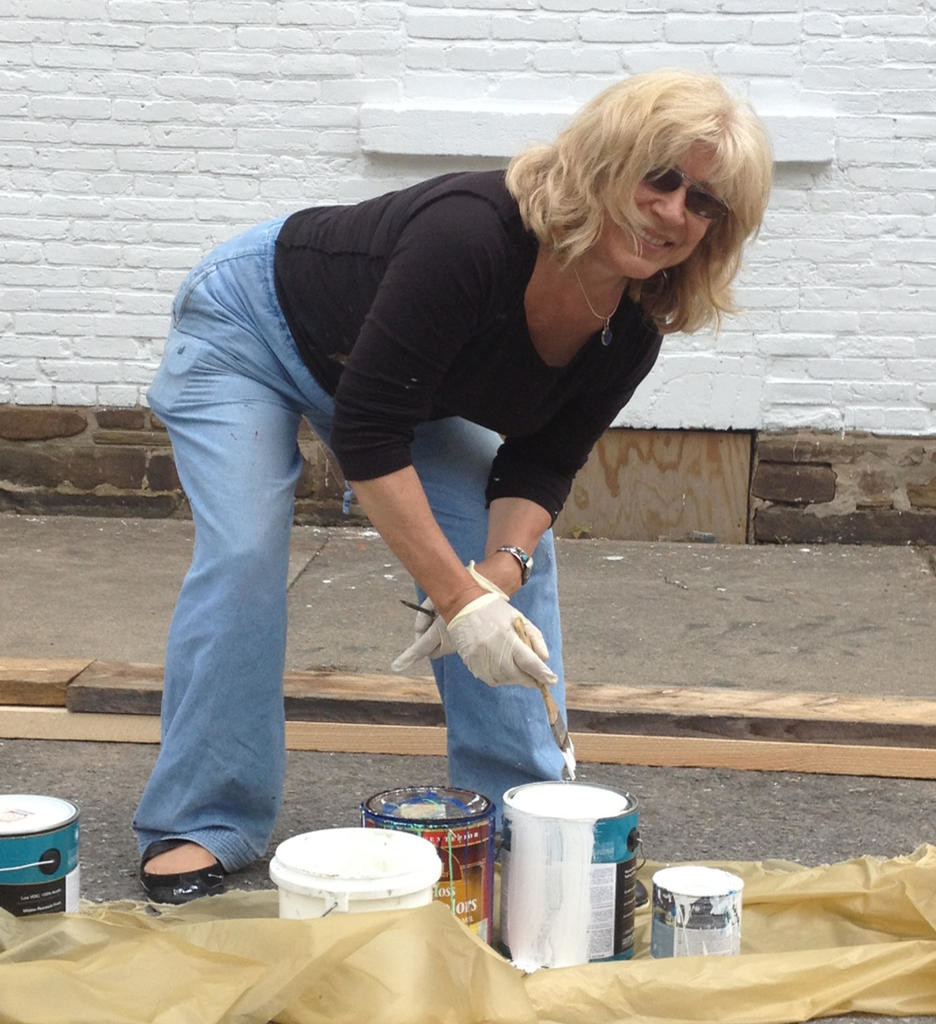 ARTIST IN ACTION — Artist and retired art teacher Jane Grace Taylor gets ready to paint the Camden Continentals mural on the VFW wall.  The mural is an enduring historic view of the renowned Camden group.