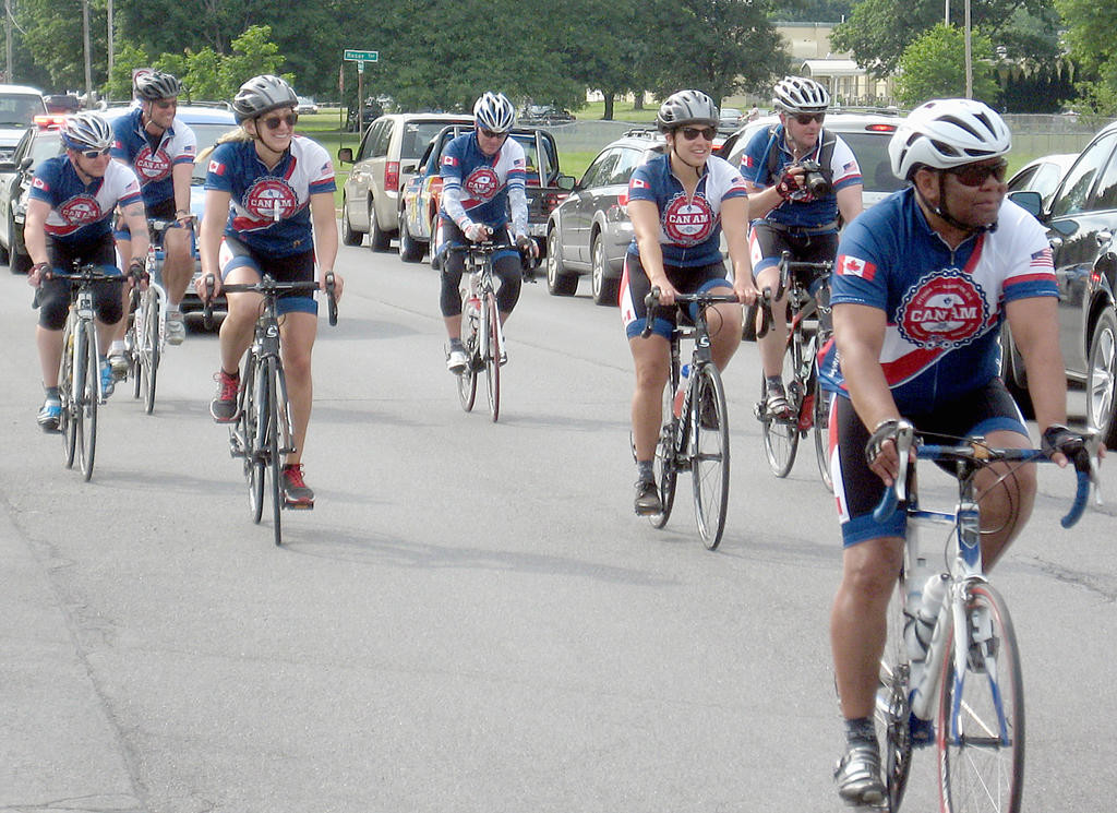 ALL SMILES — Cyclists taking part in the CanAm Veterans' Challenge, coordinated by World T.E.A.M. Sports, smile as they are greeted by enthusiastic Romans during a stop in the city Monday along their 800-mile trek.