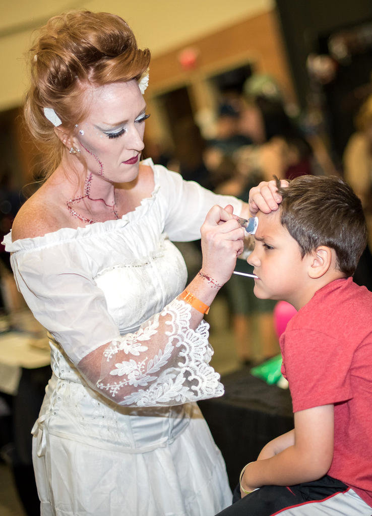 MAKEUP TUTORIAL — A ghostly zombie makeup artist shares her expertise with a young volunteer at Scare-A-Con.