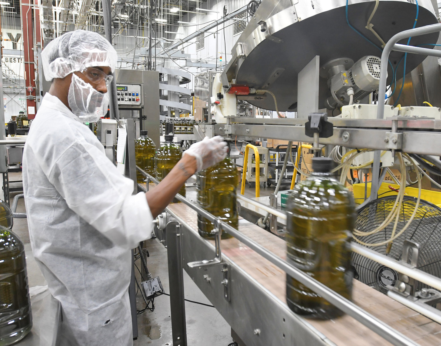 CAPPING THE PROCESS — Employee Jesse Walker conducts a quality check on caps for olive oil containers coming through the line at the Sovena USA plant at Griffiss park.