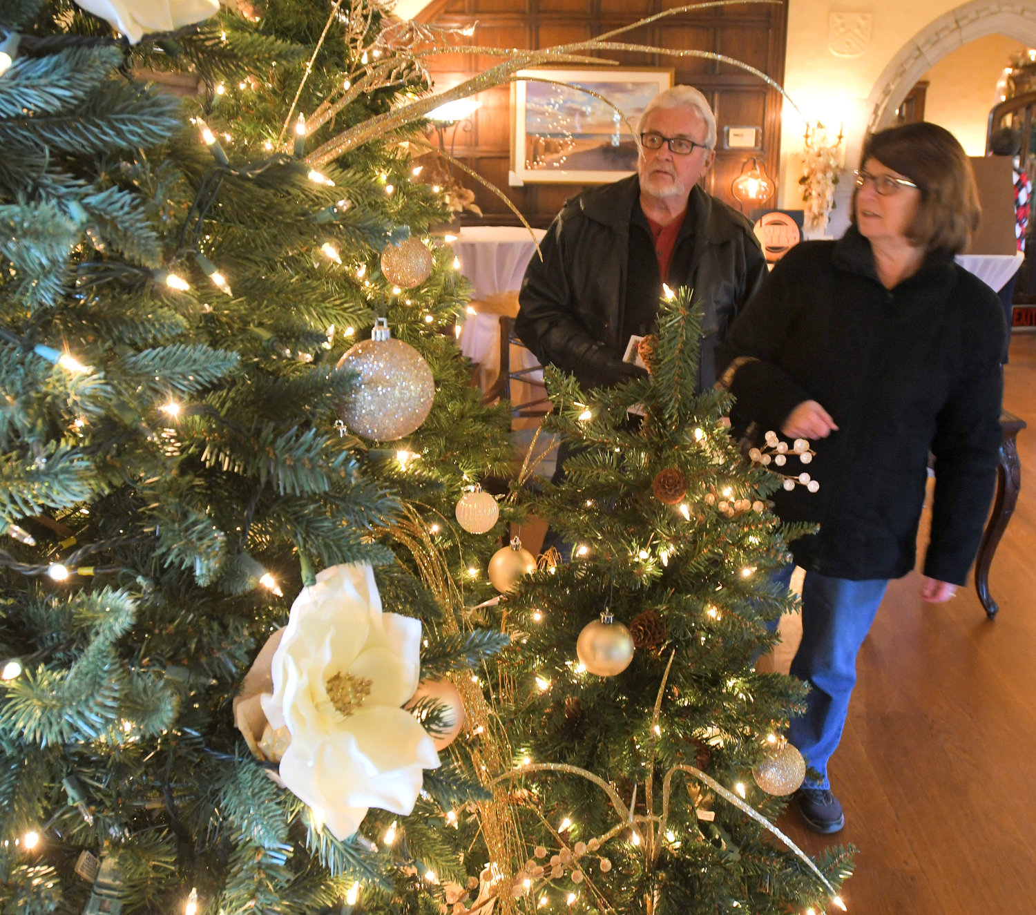 HOLIDAY HOUSE — Jerry and Maureen Switzer look over one of the Christmas trees on display at the Rome Art and Community Center during the 30th annual Holiday House event.