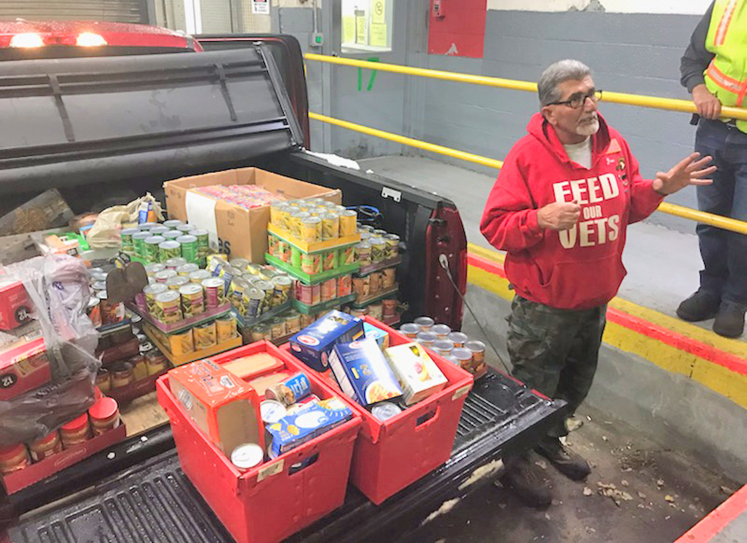 COLLECTED FOR VETS — Joe Ancona, director of the Utica Feed Our Vets pantry, stands by some of the food items collected for his organization through a drive at Worthington Industries' Rome facility.
