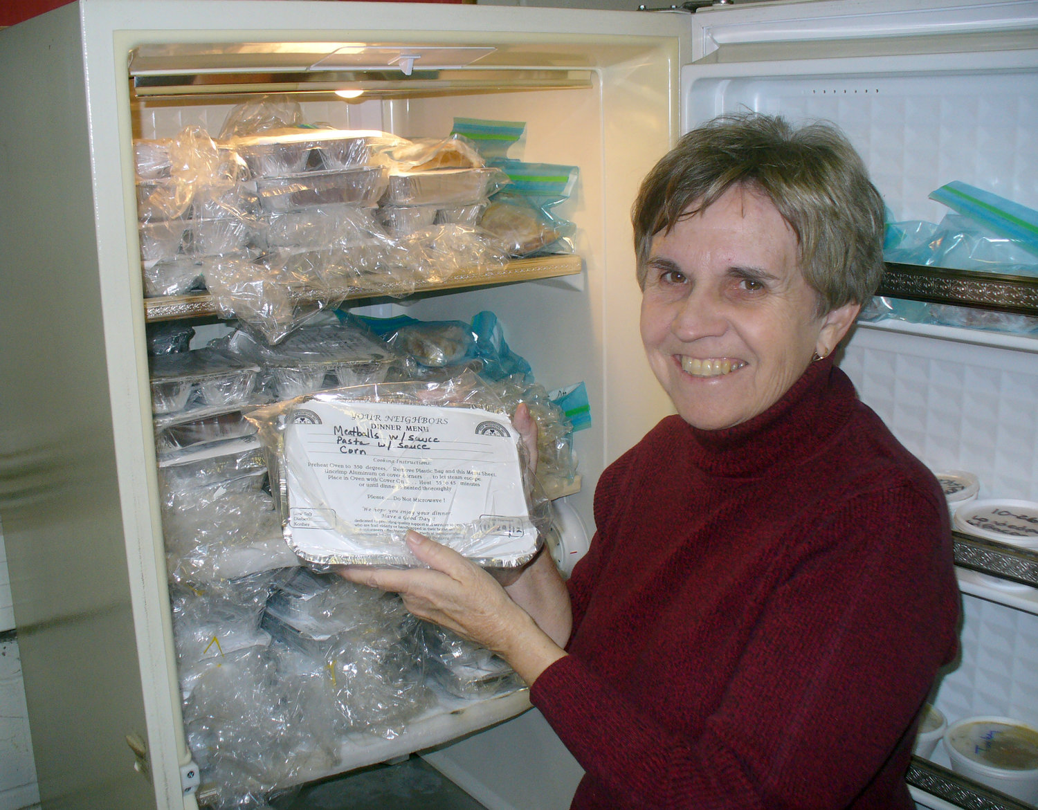 "FILLING A NEED — Long-time Your Neighbors, Inc. volunteer Carole Grove holds one of the home-cooked frozen meals that are stored in the non-profit's ""Food Bank,"" that will go to seniors in need within the community."