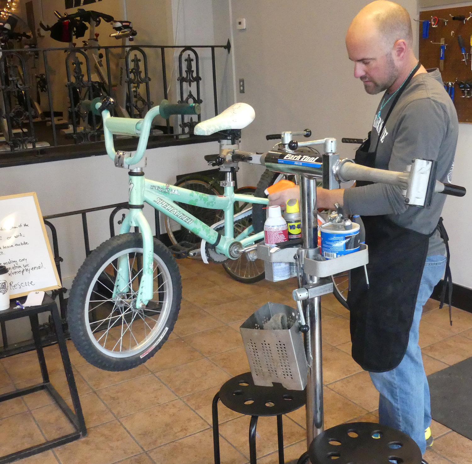 REPAIR AND MAINTENANCE — Matt VanSlyke, executive director of Utica Bike Rescue, repairs a girl's bike that will be resold while working in the organization's Clinton shop at 8 College St.