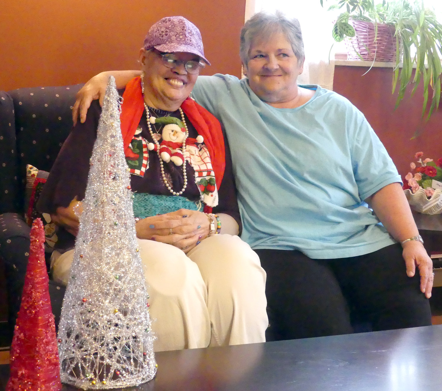 BEST BUDDIES — Both Mary Hammond of Utica, left, and Beverly Saxe, of New Hartford, are members of the Adult Daycare program at LutheranCare in Clinton. Hammond happened to be the winner last Tuesday of the Ugly Christmas Sweater Contest, which is just one of several group activities the program offers.