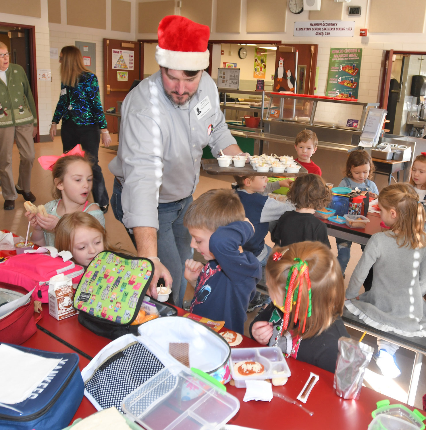 SOMETHING NEW — Clinton parent volunteer Kevin Ziesenitz hands out samples of the Asian Cabbage Slaw offered to elementary children during their lunch time at Clinton Elementary School on Dec. 18.