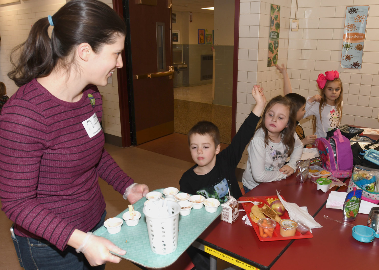 "LET ME TRY — Parent volunteer Laura Wileczka hands out cups with the Farm to School ""Harvest of the Month"" program's Asian Cabbage Slaw that was offered to children at Clinton Elementary School on Dec. 18."