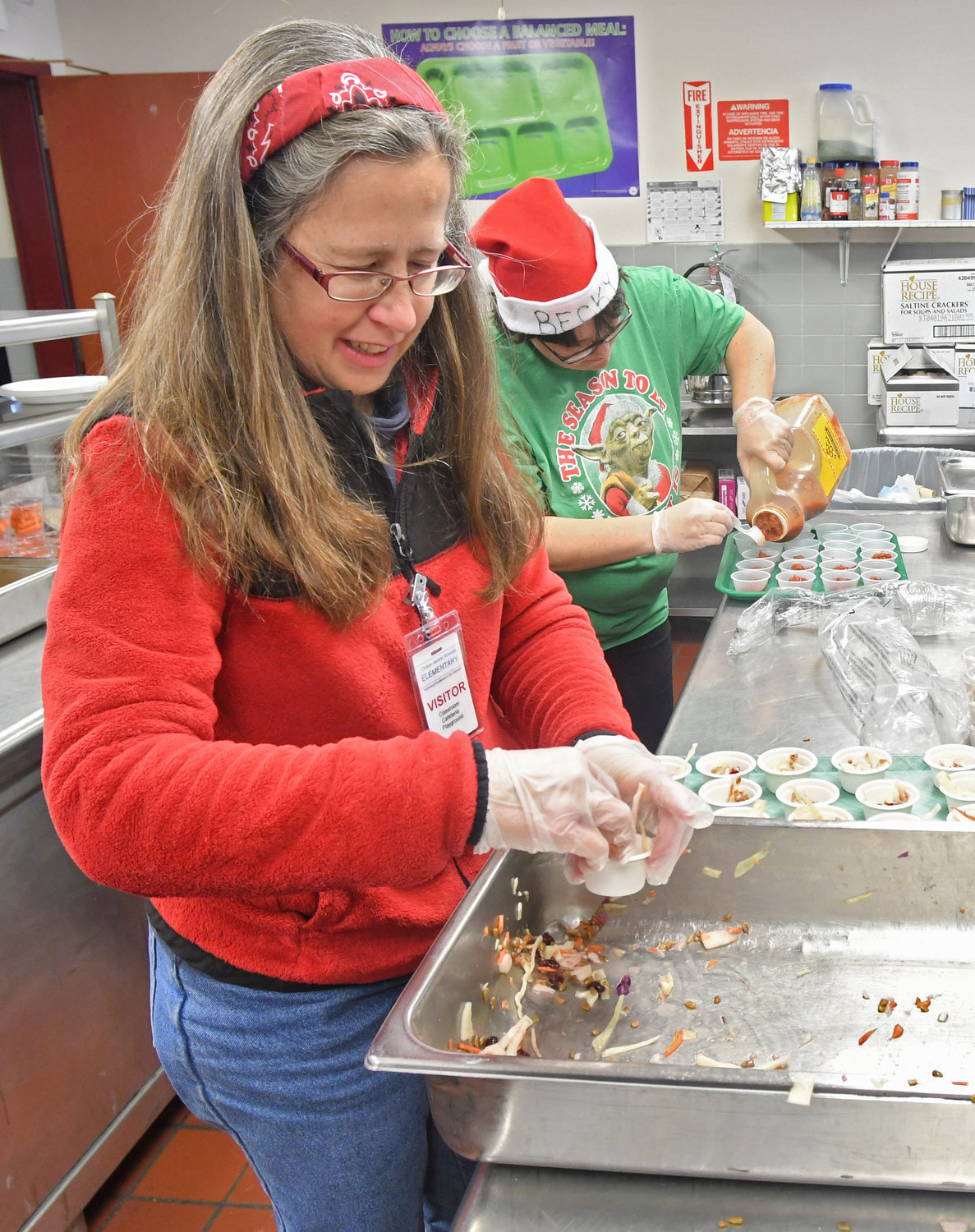 DISHING IT OUT — Clinton Elementary School parent volunteer Sarah McCullough dishes out Asian Cabbage Slaw into little cups for children to try during their lunch on Dec. 18 as part of the Harvest of the Month program.