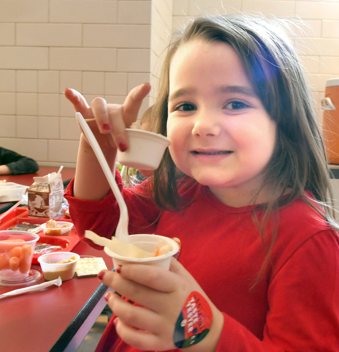 THIS IS GOOD — Clinton Elementary School kindergartener Alexandra Blum holds up the delicious Asian Cabbage Slaw that she tried during lunch on Dec. 18 as part of the Harvest of the Month program that's part of the Farm to School initiative.
