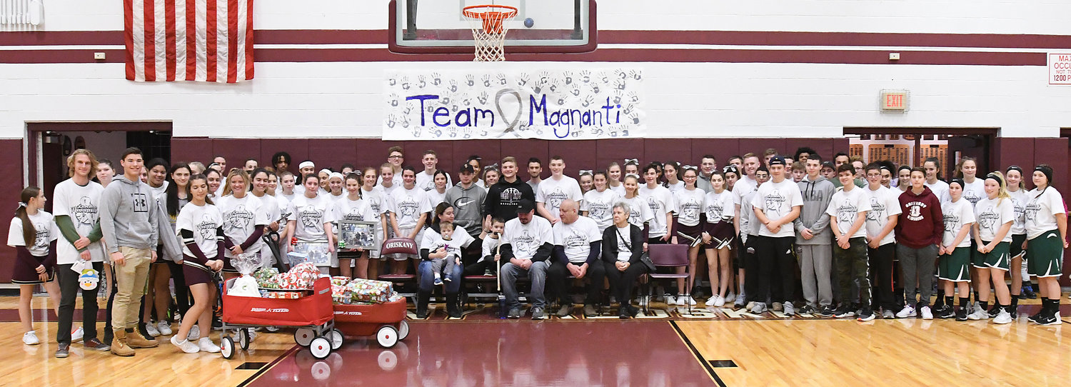 COMMUNITY SUPPORT — Students and community members came together to give the Magnanti family, of Oriskany, a good Christmas as father Kevin, Class of 1996, battles brain cancer. Magnanti was joined by his wife Alyssa, children Augie and Rocco, and his parents at the girls' varsity basketball game on Dec. 18. Oriskany students and athletes raised about $2,000 to purchase gifts for the family. Outside businesses contributed greatly to the fund-raising efforts as well. The gifts were presented to the family between the junior-varsity girls and varsity girls'  games versus Hamilton.