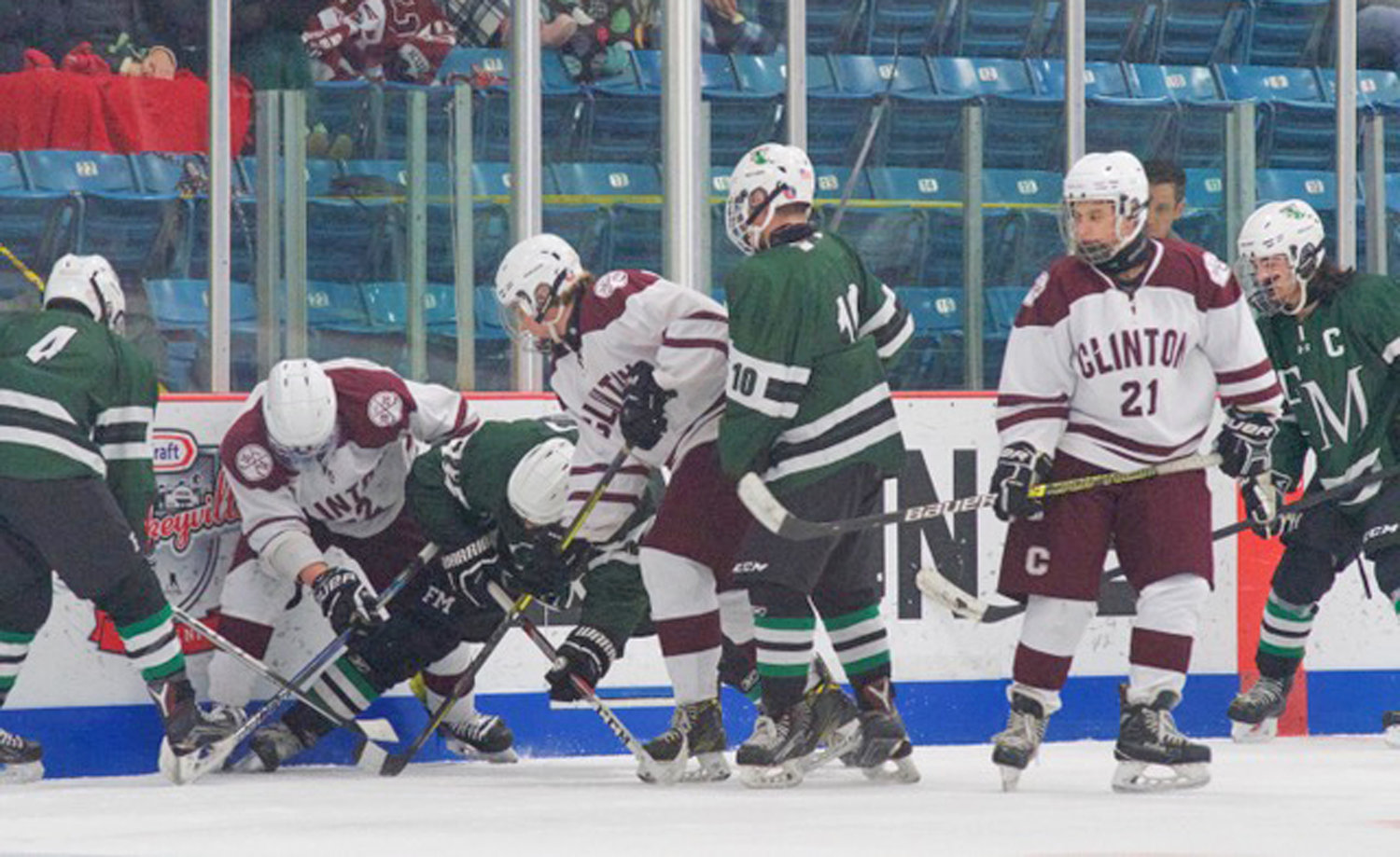 TIED UP — Players from the Fayetteville-Manlius Hornets and the Clinton Warriors battle for the puck at their feet in the Clinton holiday tournament championship game on Dec. 28 at the Clinton Arena. F-M won 2-0.