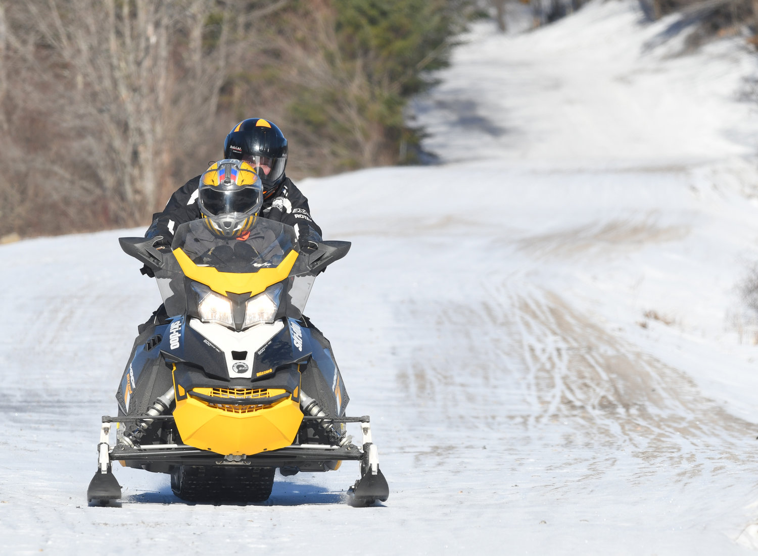 MAKING THE BEST OF IT — A lone snowmobile makes its way south on North Street in Old Forge Wednesday. The lack of snow is hampering the winter past time in the north country, but trails in the Old Forge area have kept a minimal but ridable base through recent thaws. Those in the vital snowmobile industry are encouraged by forecasts of more seasonable weather.