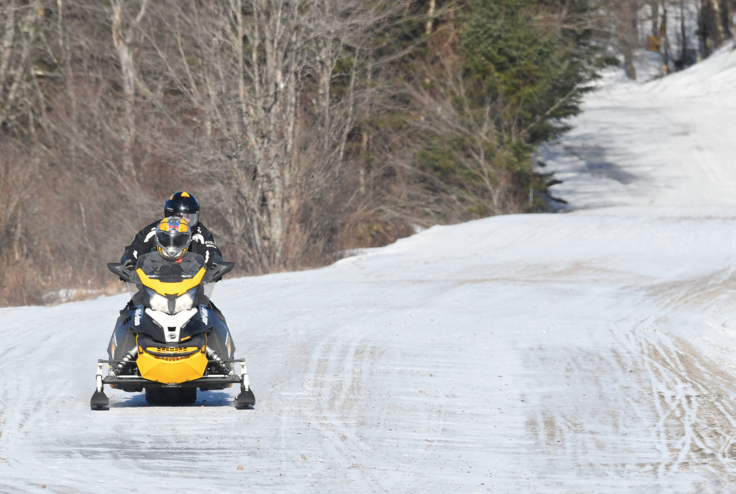 A lone snowmobile makes its way south on North St. in Old Forge on very a  thin icy trail. A lack of snow is hampering the winter past time in the north country.