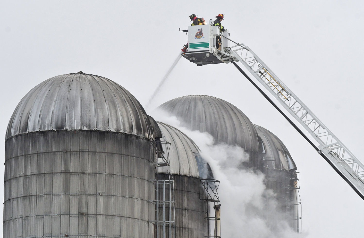 DOWN INSIDE — Firefighters in a ladder truck aim their hose line down into a silo on Whittaker Road in Trenton this morning to douse the burning feed inside. It is the second fire in less than a week for the farm, a barn caught fire from an electrical malfunction on a tractor on Sunday with some 200 head of cattle killed. See story, page 2.