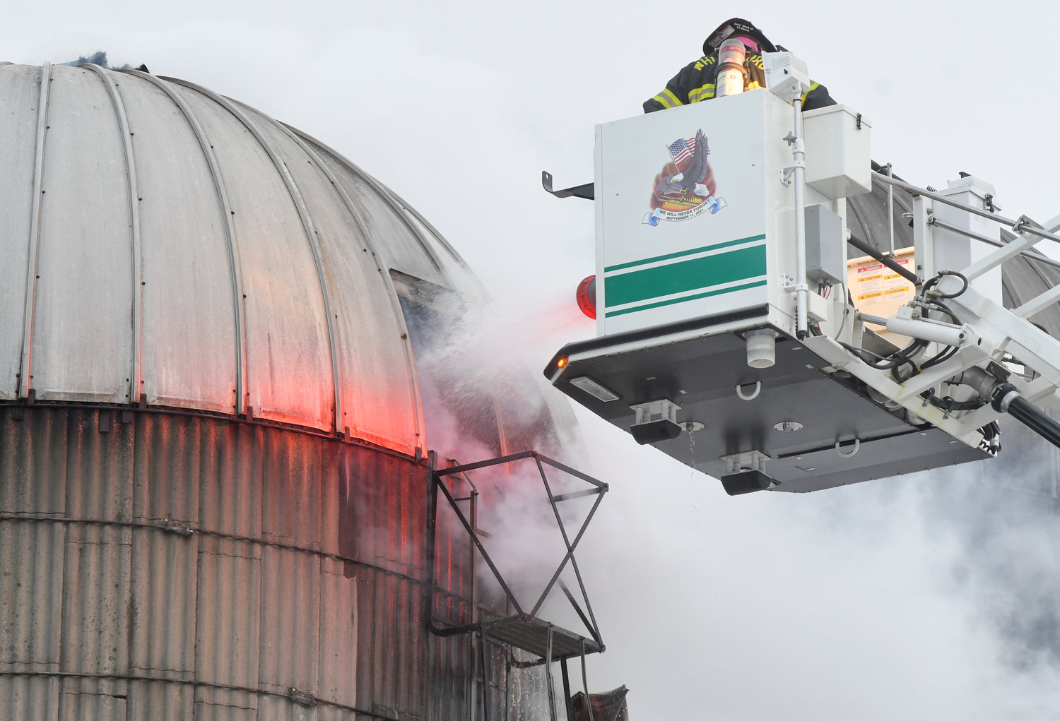 TAKING AIM — Whitesboro firefighters use their ladder truck to get to the top of a silo in Trenton this morning, so they can blast water in through the access hatch.