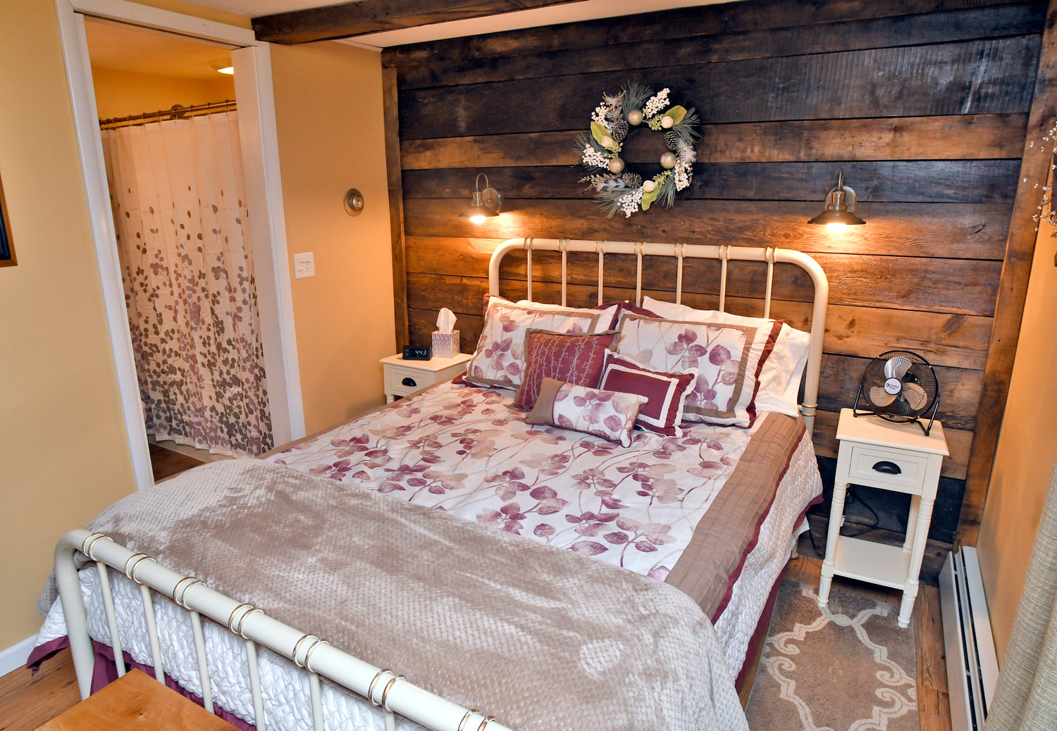 QUAINT SPACE — The bedroom at Beatty Bed and Biscuit, 21 Beatty Ave., Clinton, features a queen size bed with comfortable foam mattress and a wall adorned with original barn wood.  Dogs are invited to sleep there as well.