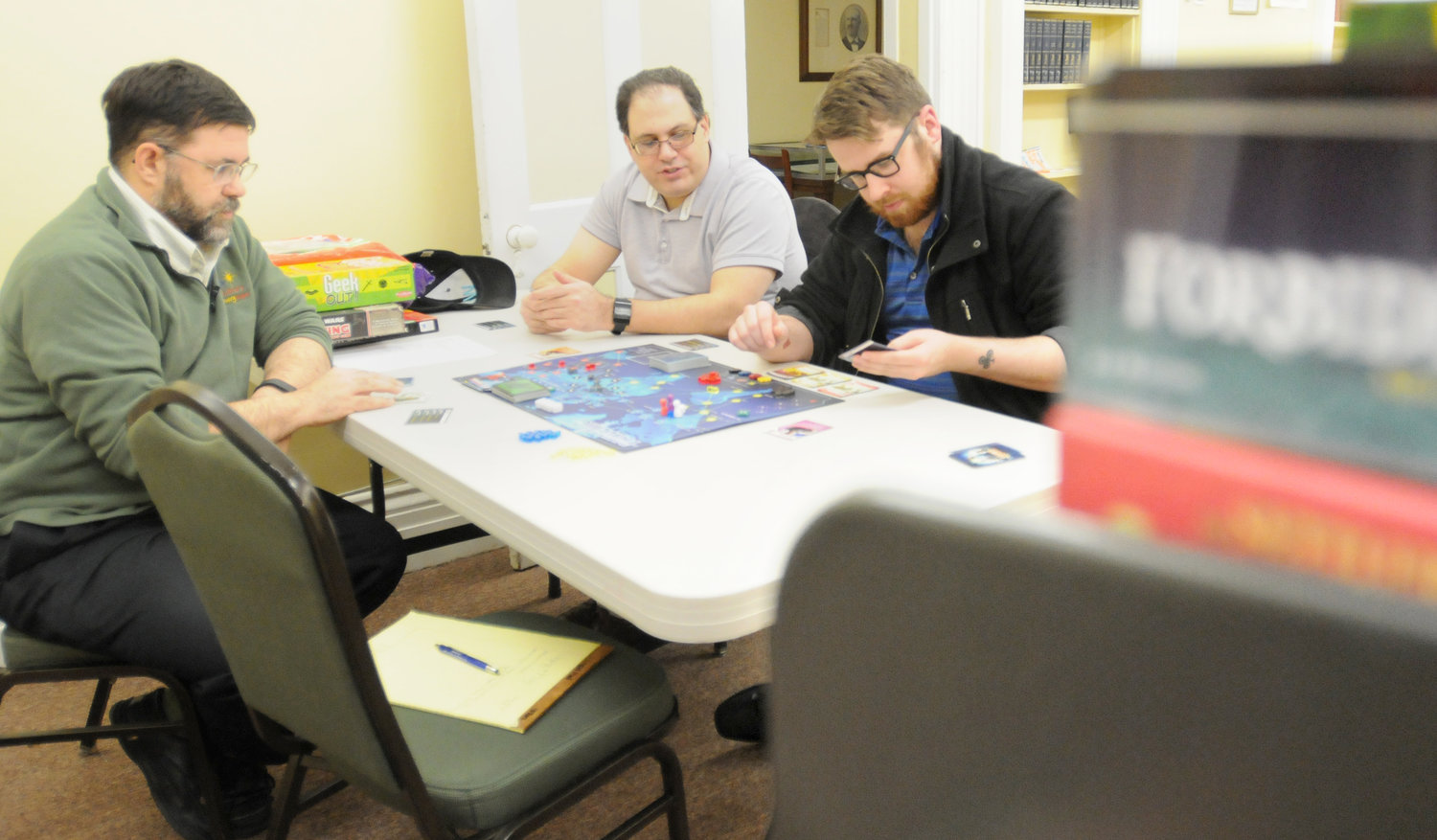 GAME NIGHT — Peter Chien, Unplug and Play organizer and librarian at Jervis, Michael Magliocca, and Brennan Pimpinella gather around a table at the library to play Pandemic.