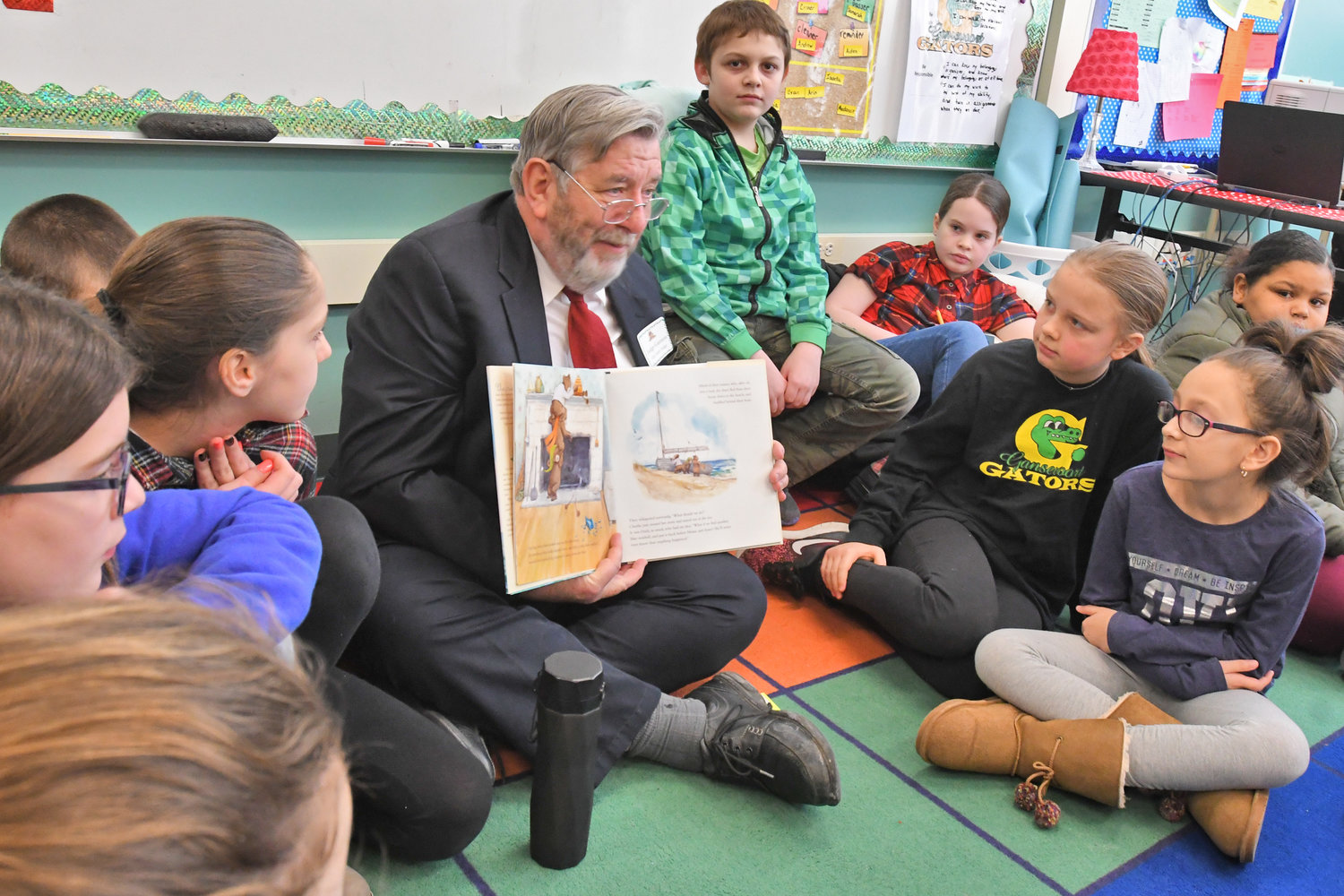 "READING WITH THE JUDGE — Rome City Court Judge John C. Gannon sits on the floor to read a book with a fifth-grade class at Gansevoort Elementary School this morning as part of a ""Community Readers Day"" in conjunction with the overall ""World Read Aloud Day"" observance. Gansevoort librarian Keri Citriniti organized the school's event, which involved 18 persons from the community including a reader for each class throughout the school."