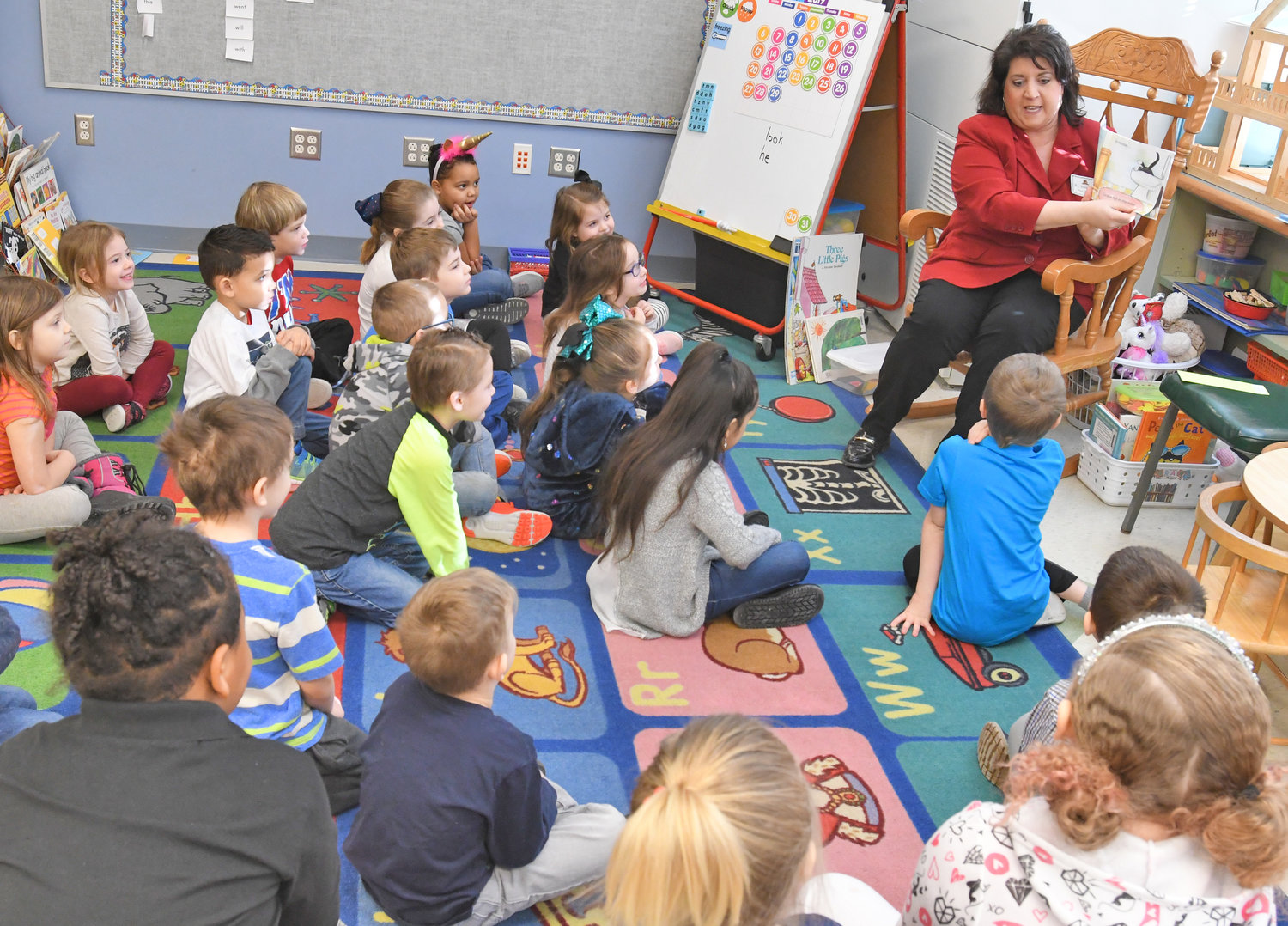 "FROM COLLEGE TO KINDERGARTEN — Franca Armstrong, dean of Mohawk Valley Community College's Rome campus, reads to a kindergarten class at Gansevoort Elementary School this morning for a ""Community Readers Day"" in conjunction with the overall ""World Read Aloud Day"" observance. The Gansevoort event, organized by school librarian Keri Citriniti, included 18 persons from the community, with a reader for each class throughout the school."