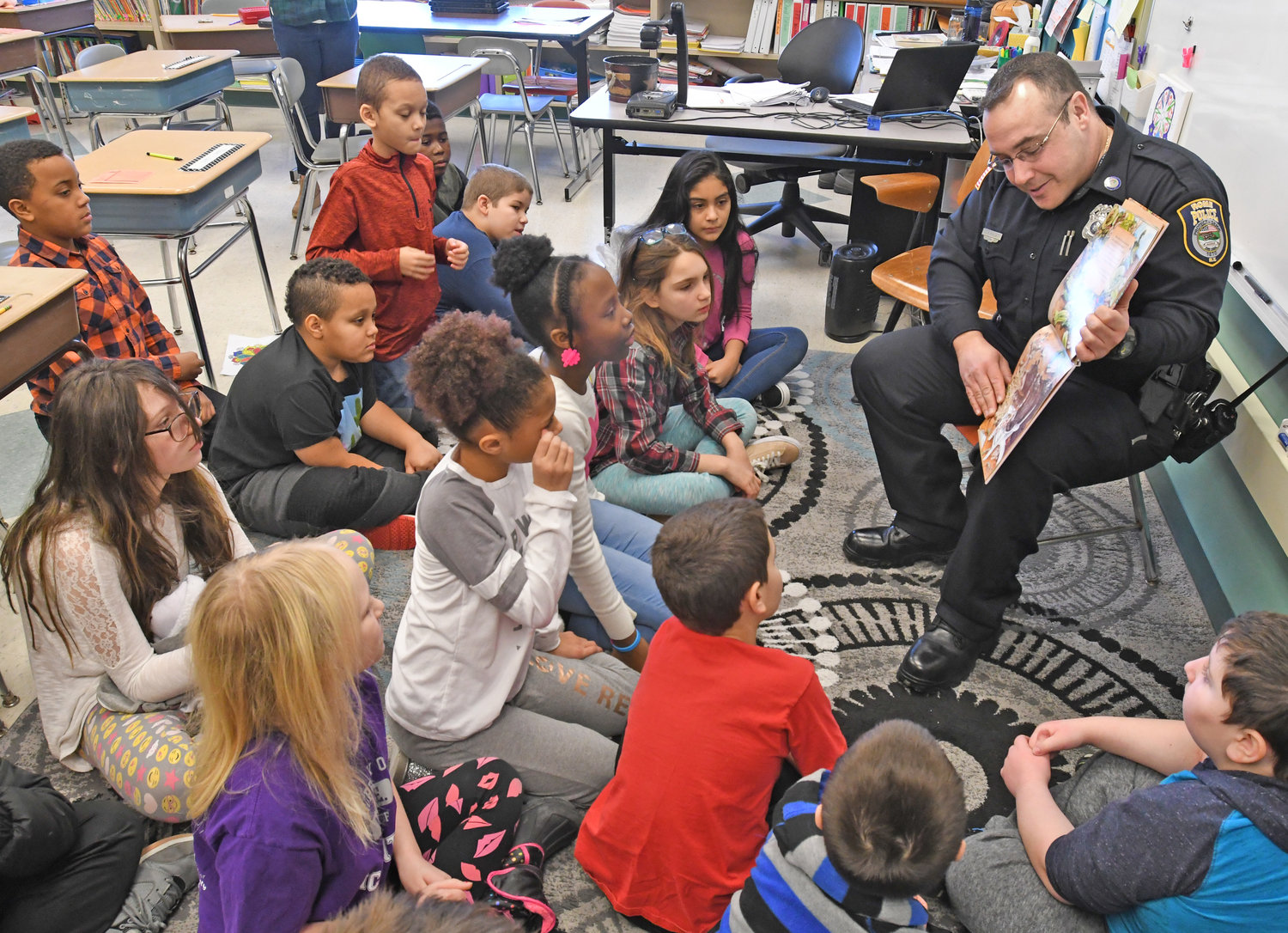"BY THE BOOK — Rome Police Department officer Shane Riolo reads to a fourth-grade class at Gansevoort Elementary School this morning for a ""Community Readers Day"" event in conjunction with ""World Read Aloud Day."" He was among 18 readers from the community, including one for each class at the school, in the school activity that was organized by Gansevoort librarian Keri Citriniti."