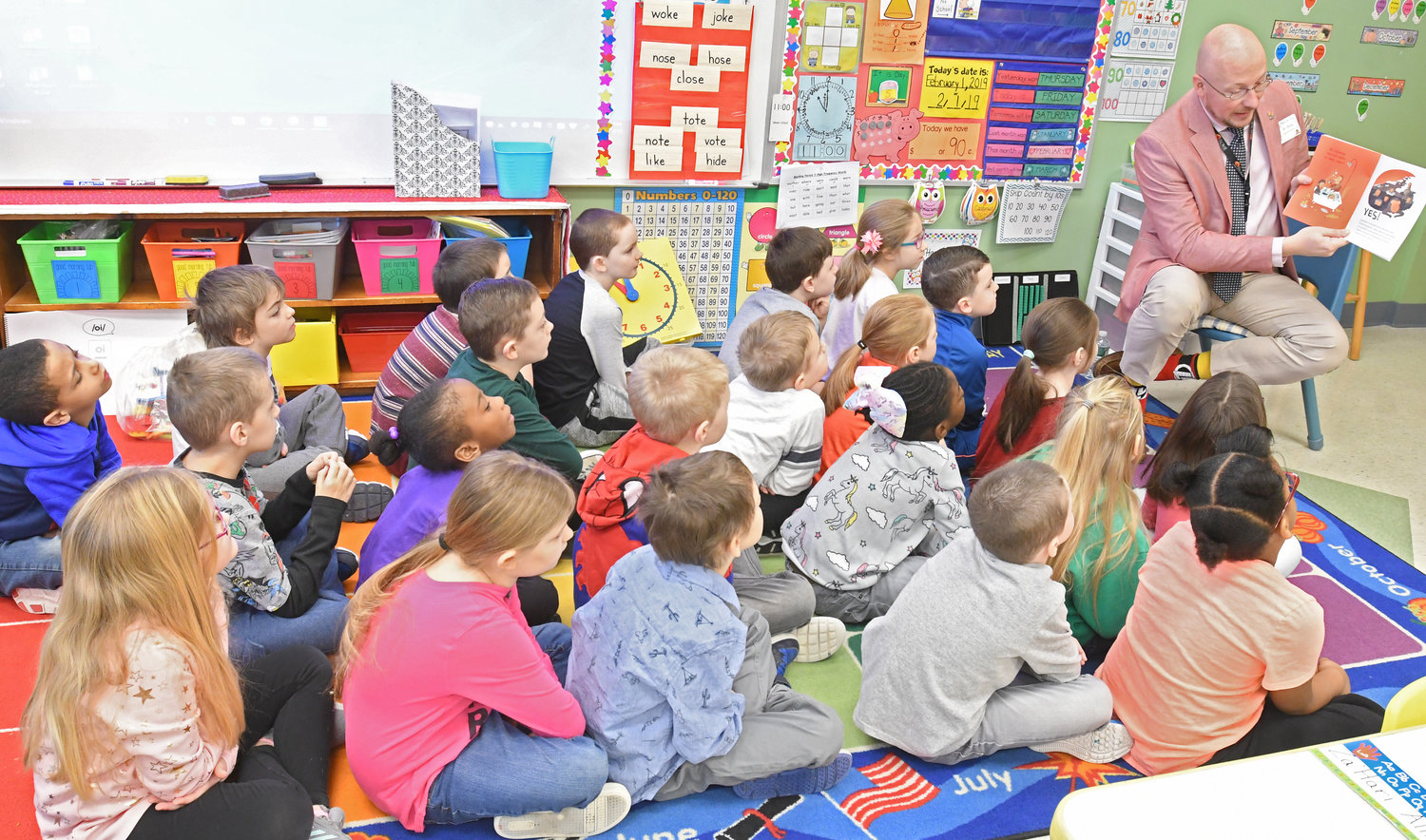 "TALES FROM SCHOOL SUPERINTENDENT — Rome school district Superintendent Peter C. Blake reads to a first-grade class at Gansevoort Elementary School this morning, as part of ""Community Readers Day"" at the school in conjunction with the overall ""World Read Aloud Day"" observance. Every class in the school participated in the event, which was organized by Gansevoort librarian Keri Citriniti and included 18 readers from the community."