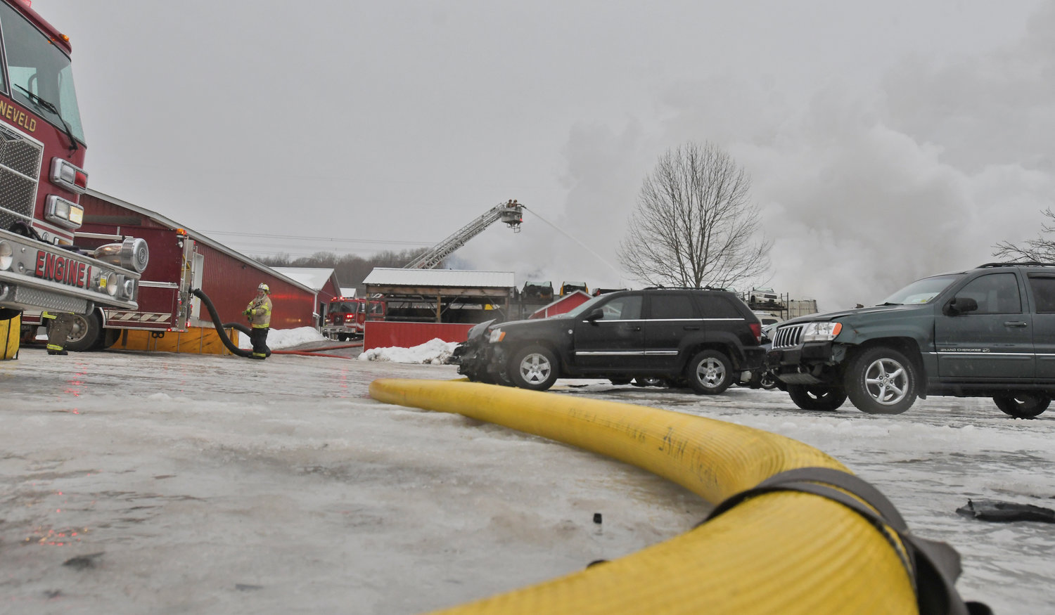WATER EVERYWHERE — Firefighters fill up a portable pond at the scene of a large fire at Tolpa's Auto Parts on French Road in Steuben this afternoon. Water had to be tankered to the scene from multiple fill sites, while crews also slogged through freezing rain.