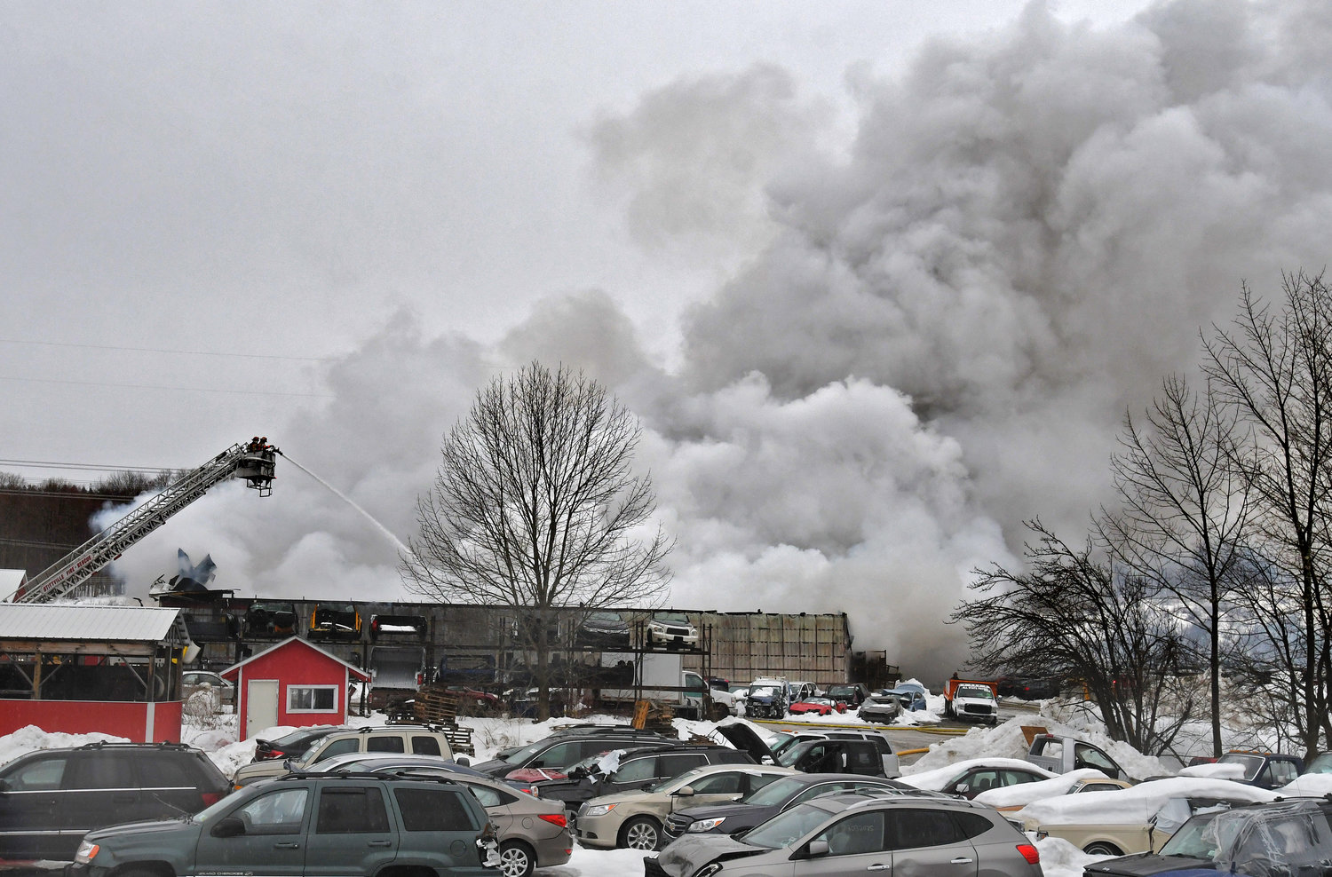 THREE GARAGES LOST — Heavy smoke billows into the air as a Stittville ladder truck blasts water down into a large fire at Tolpa's Auto Parts off French Road in Steuben. Fire officials said three workshops were lost in the blaze.