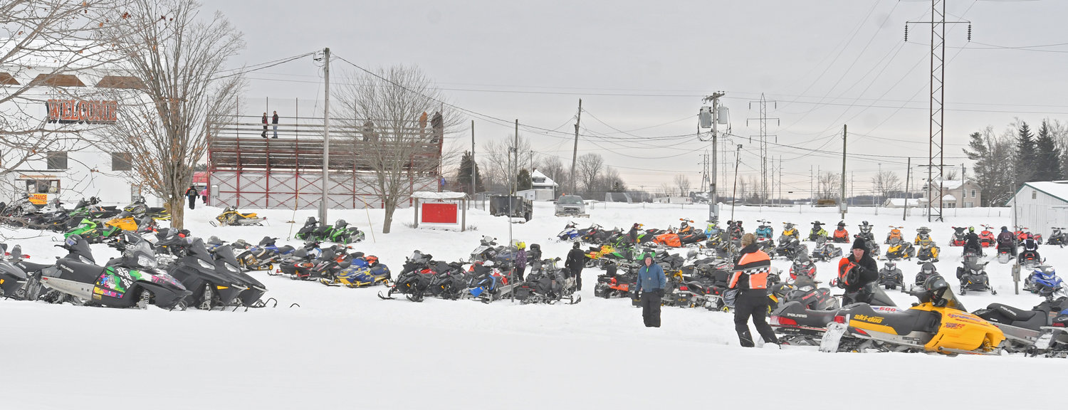 PARKING LOT — Snowmobiles line the parking lot at the annual Boonville Snow Festival on Saturday afternoon. For many spectators, there was no better way to get to the snowmobile races than on their own sleds.