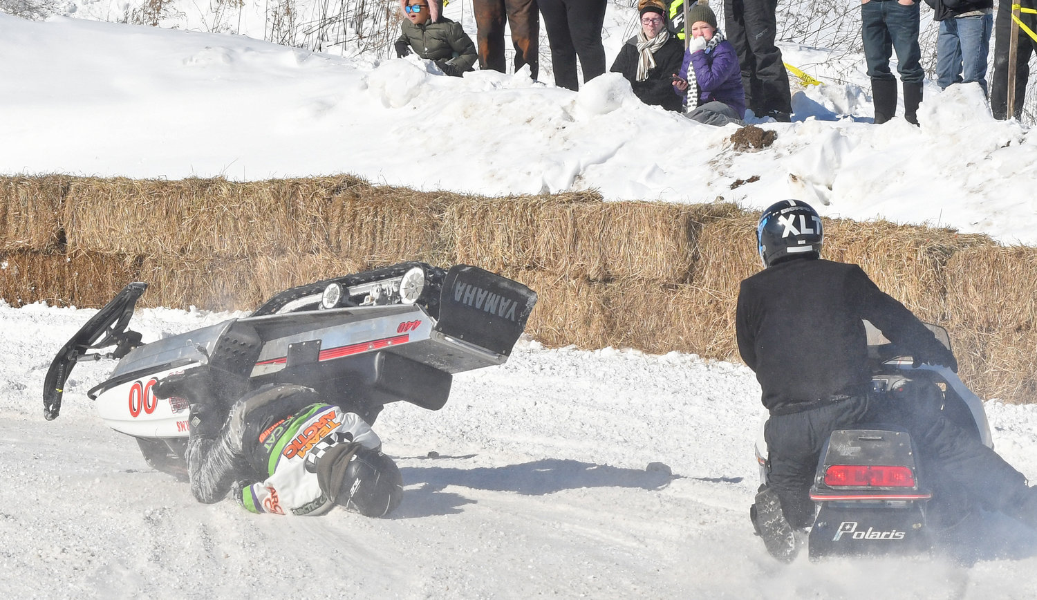 Randy Storms gets upside down with the sled rolling over on top of him at the Old Dog Races in Taberg on Saturday.