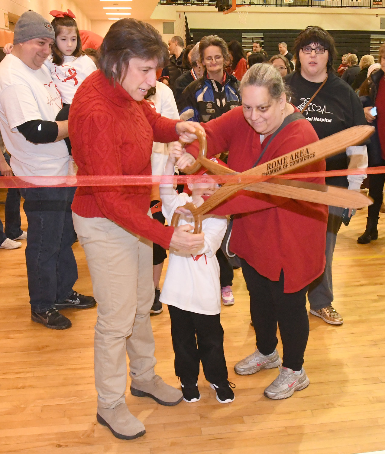 Mayor Jacqueline M. Izzo helps cut the ribbon on the heart walk with Red Cap Ambassadors Jaxon Hayes and Angel Woolheater.