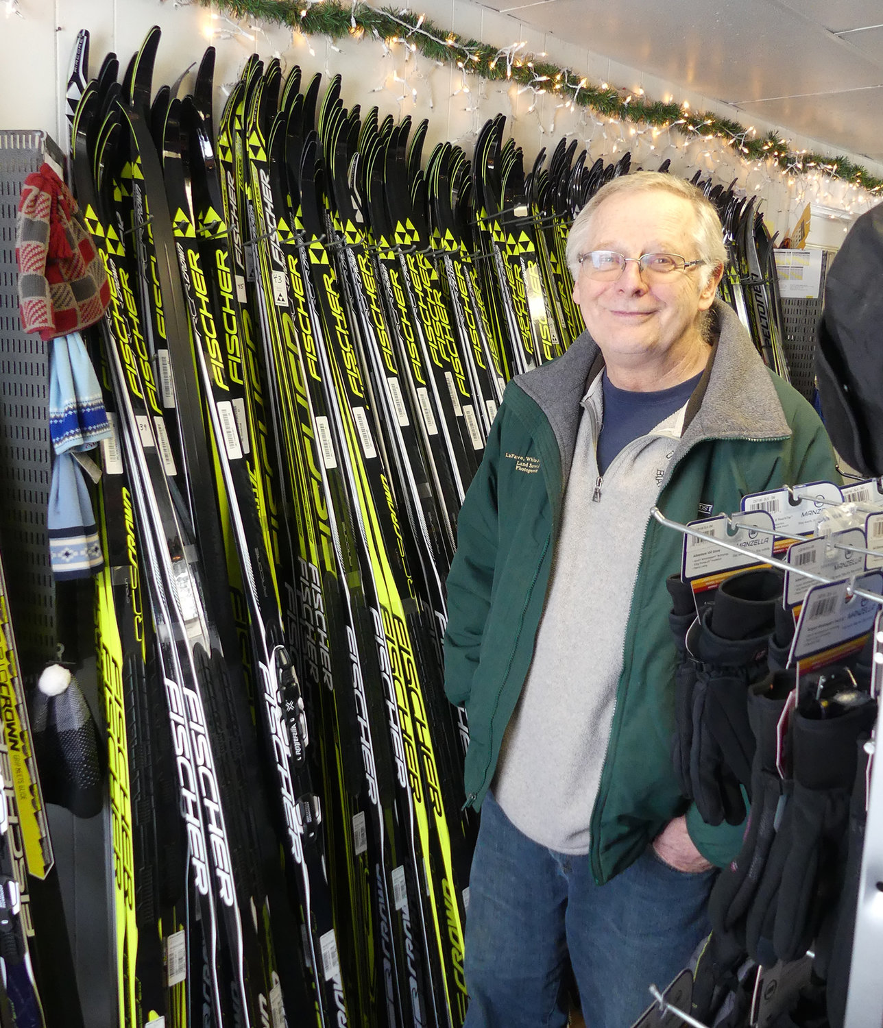 SKI CENTER — Hugh Quinn poses by skis for sale in the retail shop at Osceola-Tug Hill Cross Country Ski Center. The shop is part of the business that is for sale as Quinn and his wife, Anna, hope to leave it in new hands and retire by the end of next ski season.