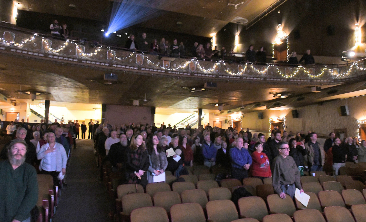 "90TH BIRTHDAY — Audience members rise for the national anthem at the Capitol Theatre's 90th anniversary program on Dec. 10, 2018. The program recreated the showing on the theater's opening night, featuring the silent film ""Lilac Time"" with musical accompaniment on a Moeller theatre organ."