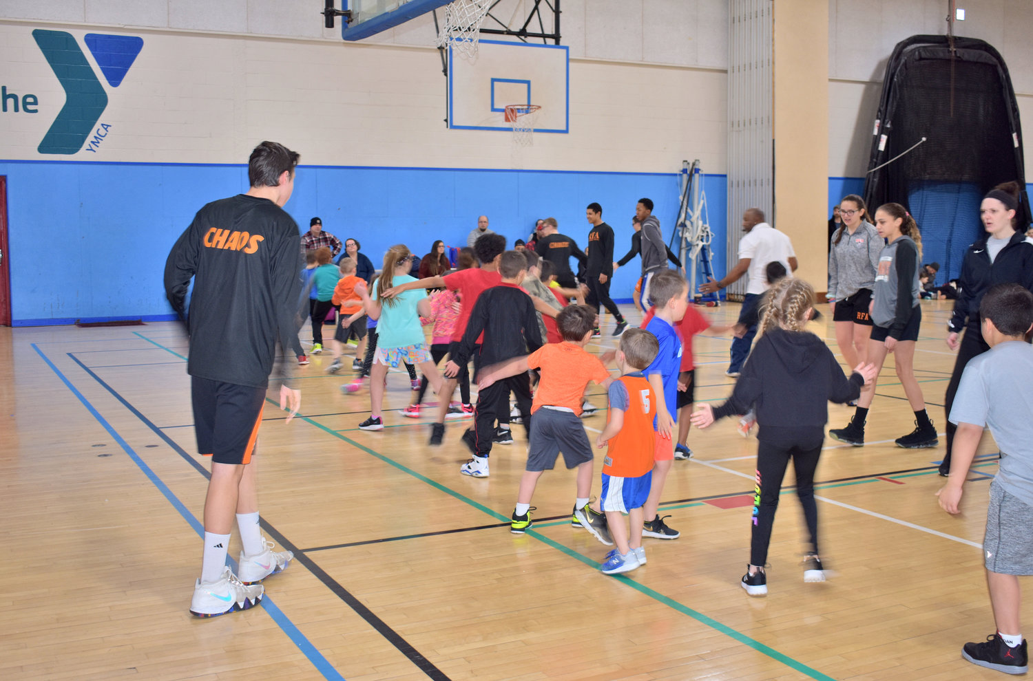 TEACHING AND LEARNING — Members of the Rome Free Academy boys and girls varsity  basketball teams help instruct youth in grades kindergarten through second during a recent learn to play basketball clinic session.