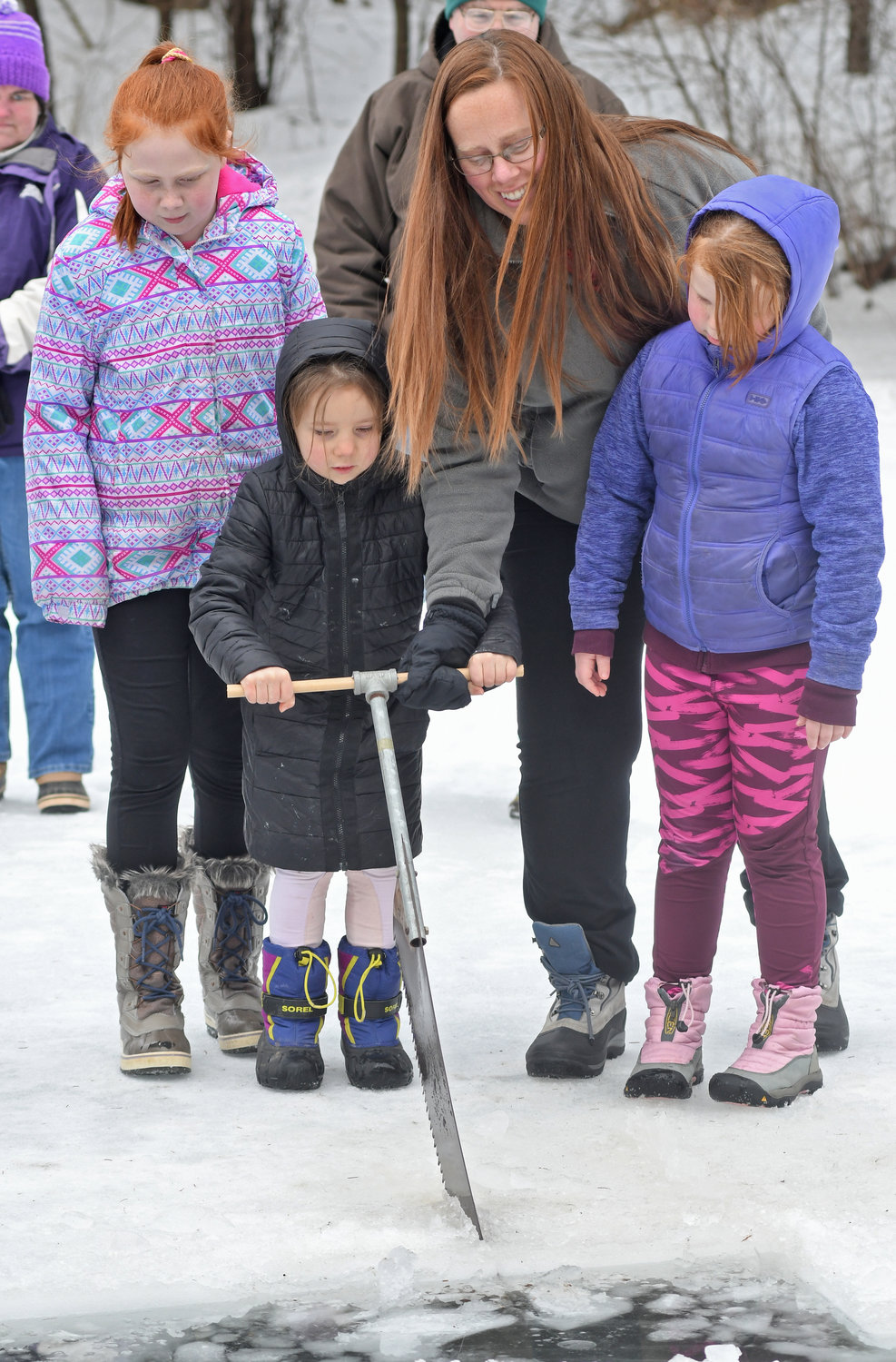 CUTTING BLOCKS — Hadley Scherer, 10, her mom Kyla Scherer and Scarlett Scherer, 8, watch and help Hazel Fox, 5,  cut ice blocks out at the Rogers Center on Satruday afternoon.