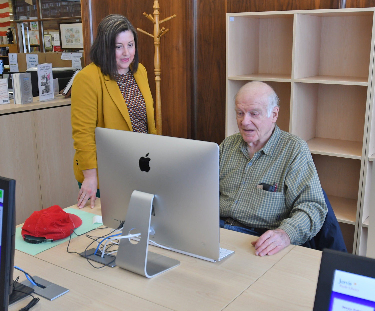 HELPING HAND — Jervis Pubilc Library Assistant Director Kari Tucker helps Jim Small navigate the net in the library's new computer lab. In addition to all new computer equipment, the library held 50 drop-in tech help sessions in 2018, providing 148 patrons with one-on-one tech assistance. Story, page 2.