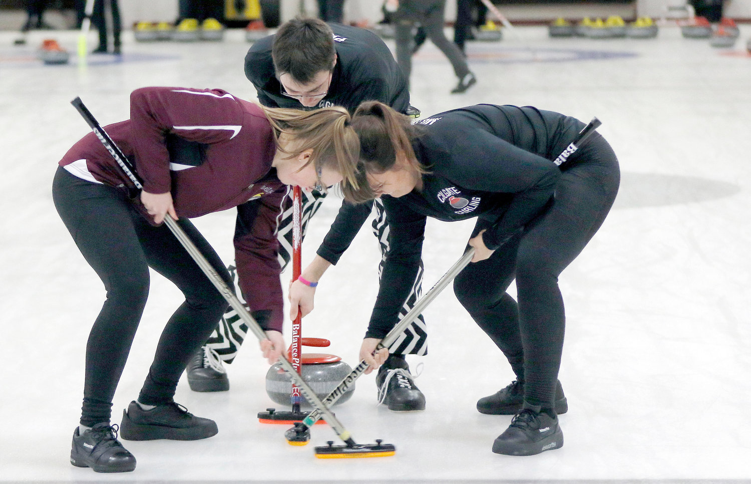 RAIDERS ON THE ICE — Colgate team members sweep ahead of a rock during the college curling national championship on Friday in Wayland, Mass.