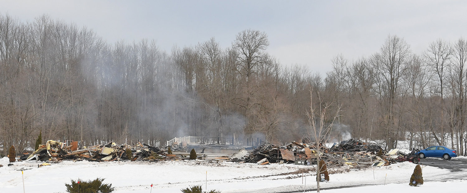 ALL THAT remains —Steam and smoke rises from the ashes of a house that was destroyed by fire at 4327 Wood Creek Road in Verona on Tuesday. Numerous departments from across the area were called in to fight the fire.
