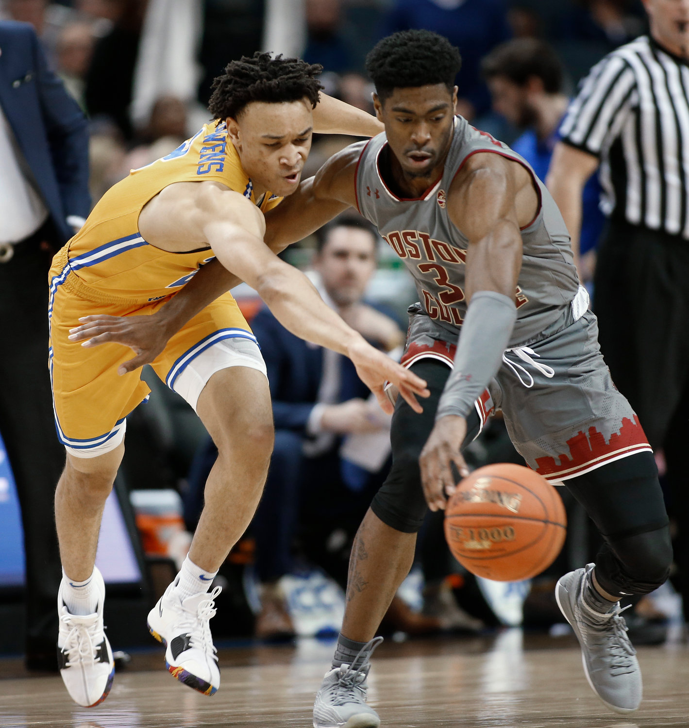 LOOSE BALL — Pittsburgh's Trey McGowens, left, and Boston College's Jared Hamilton chase the ball during the first half of Tuesday's ACC Tournament first-round game in Charlotte, N.C. McGowens scored 26 points as Pitt advanced to a second-round game tonigiht against Syracuse with an 80-70 victory.