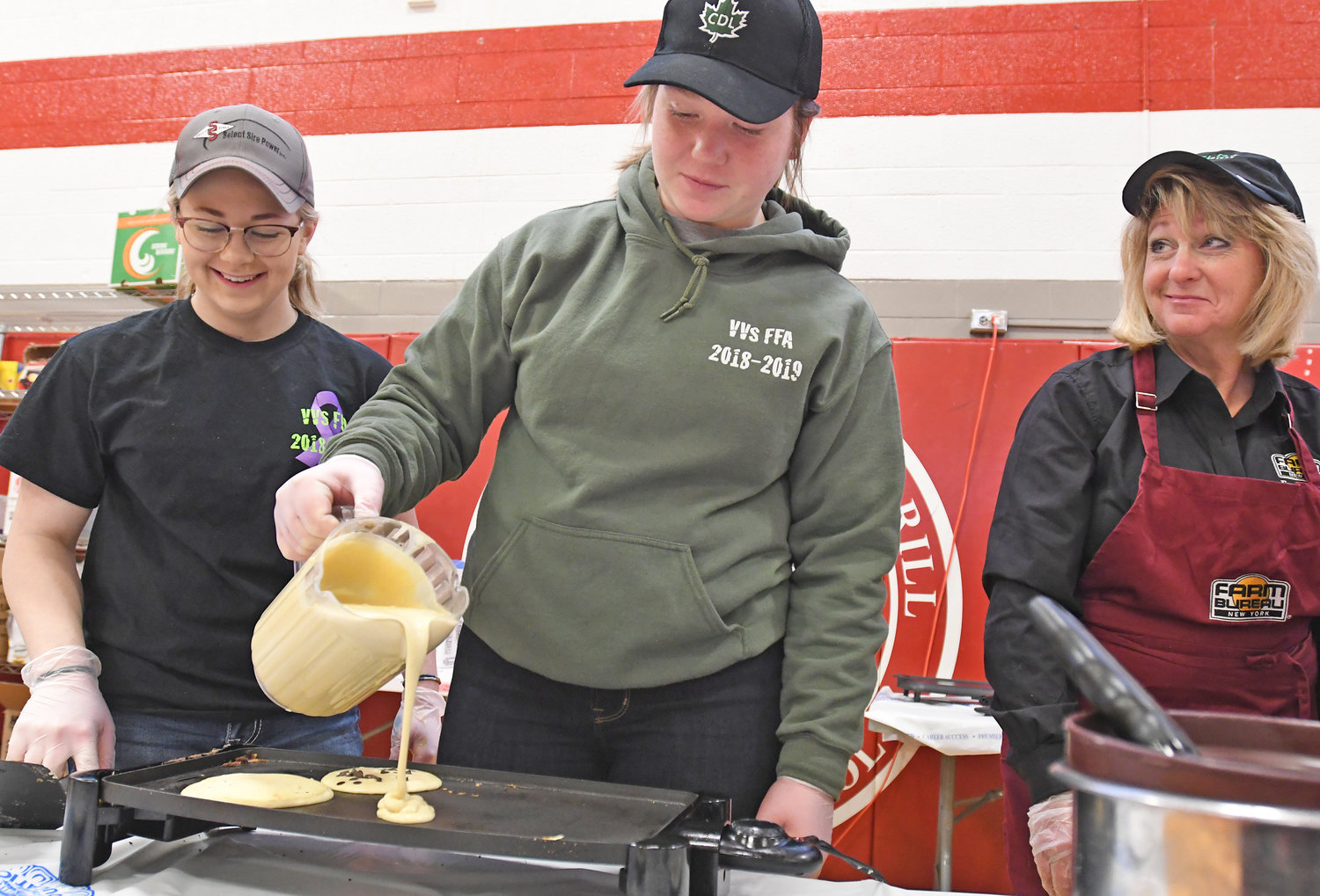 BATTER UP — Gabby Adams, left, president of VVS FFA, and Karen K. Lohr, right, watch as Danann Lohr, vice president of VVS FFA, pours the pancake batter on the griddle this morning at the VVS FFA pancake breakfast Saturday morning.