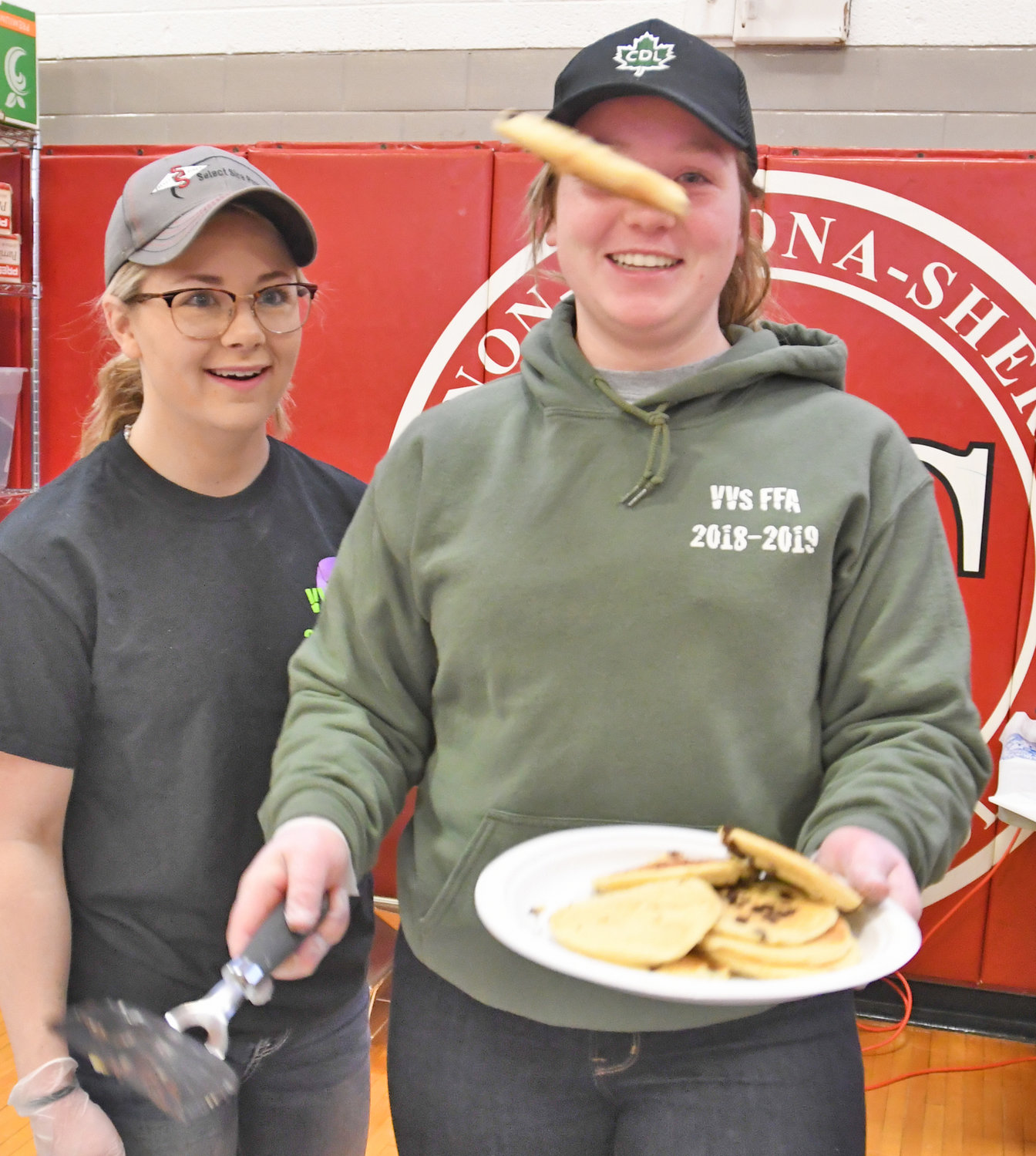 FLIPPING FOR FLAP JACKS — Gabby Adams, left, president of VVS FFA smiles as Danann Lohr, VP of VVS FFA, flips a pancake on to a plate this morning. The VVS Future Farmers of America are celebrating Maple Weekend today and Sunday, as well as March 30, 31.