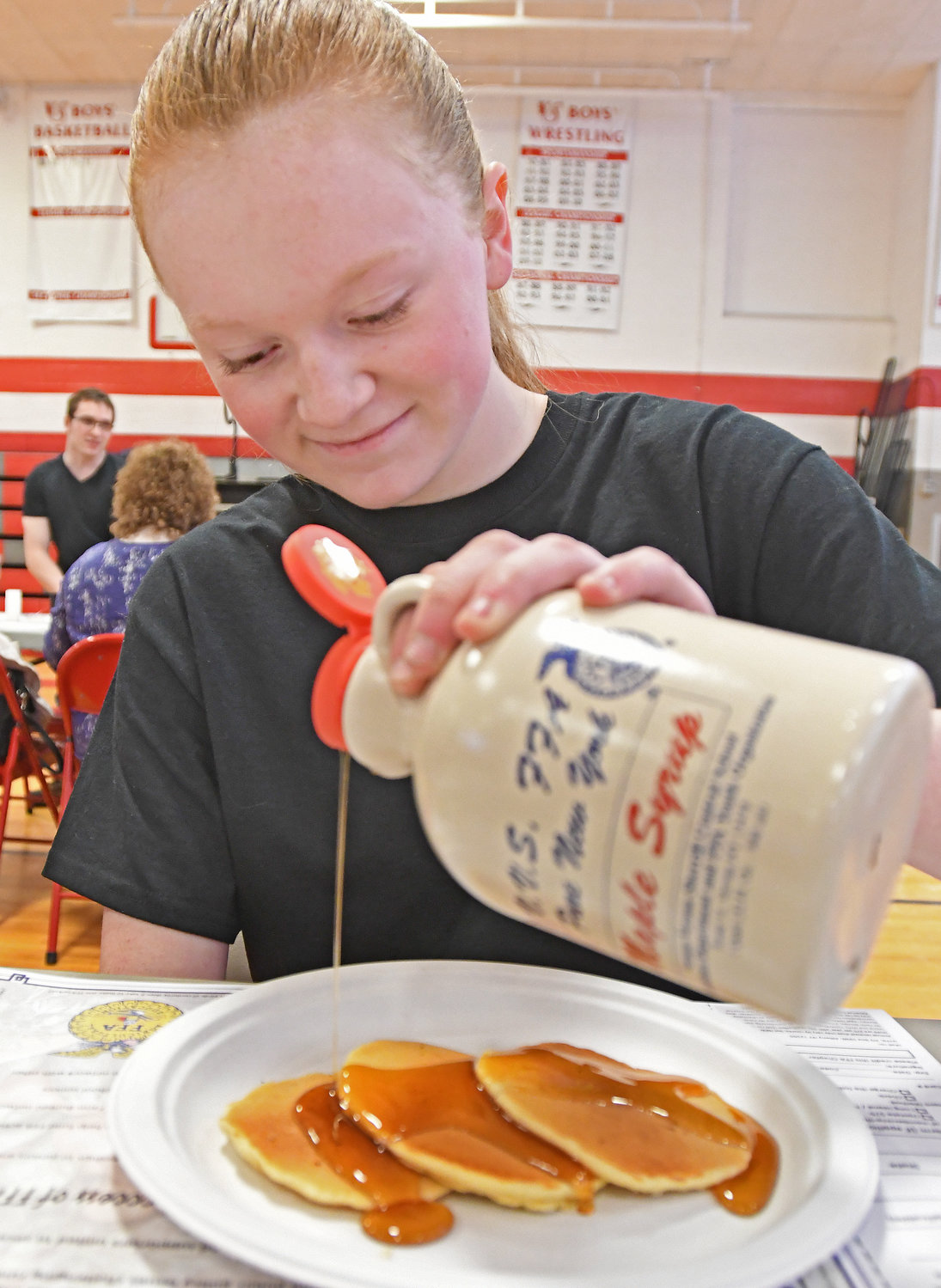 FRUITS OF THEIR LABOR — VVS FFA Secretary Rachel Champney is set to enjoy a trio of pancakes by pouring the maple syrup the school produces and sells. Go online to www.mapleweekend.com.