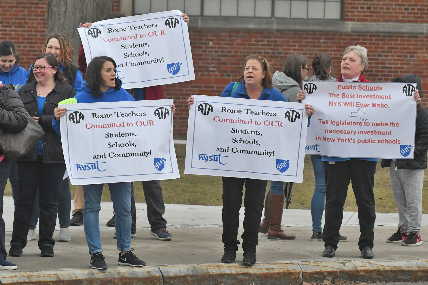 SEEKING SUPPORT — Rome teachers hold signs as they rally for additional school aid and in opposition to potential cuts as part of the Rome City School District's 2019-20 budget before Thursday night's school board meeting at Strough Middle School.
